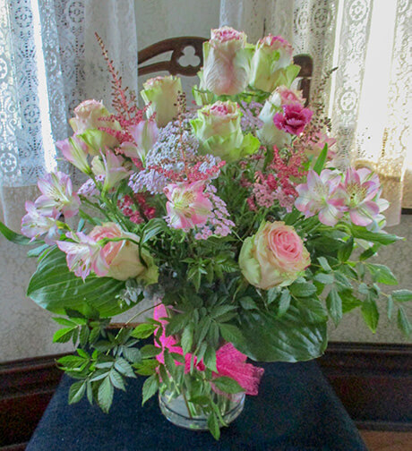 A full vase of twelve roses harmonized with accent flowers and greens.