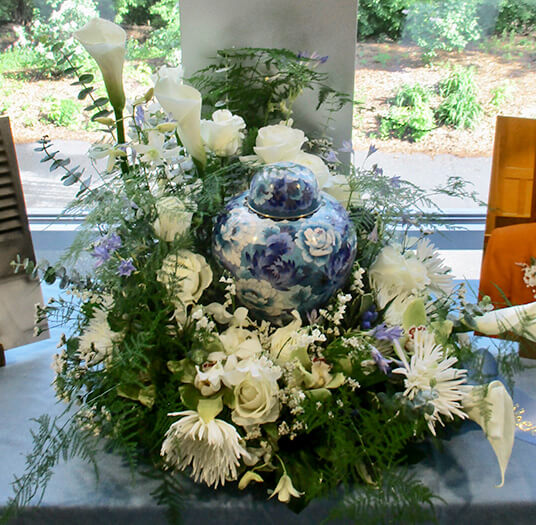 The urn is placed on an elevated center surrounded by lush blooms.
