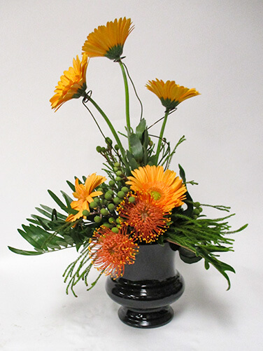 Tropical greens are mixed with gerbera daisies and pincushion proteas.