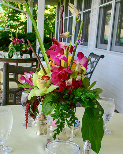 Orchids and Tropicals flower centerpiece in cylinder vase.