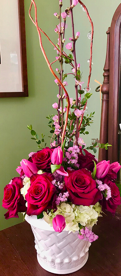 Graceful roses surrounded by hydrangeas, seasonal blooms, accents and seasonal branches.