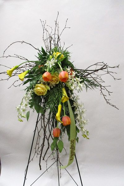A cross structure with branches embellished with beautiful blooms.